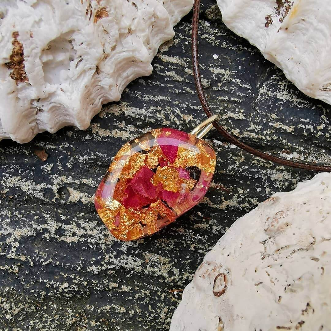 Rose and gold leaf resin necklace surrounded by shells